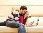 Young happy couple working on laptop — Stock Photo
