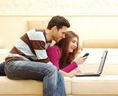 Young happy couple working on laptop and smiling — Stock fotografie