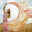 The young woman in the field holding scarf to wind. - Stock Photo
