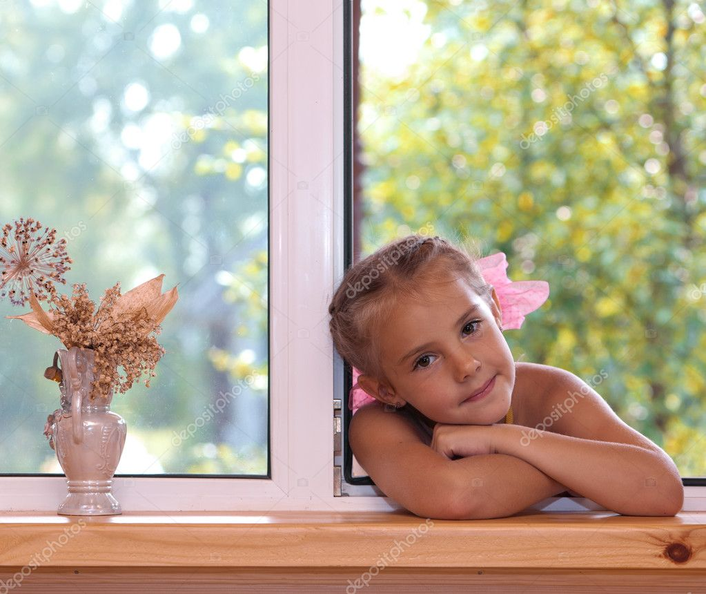 A portrait of a six-year girl  in the window in the afternoon.  Stock Photo #3685498