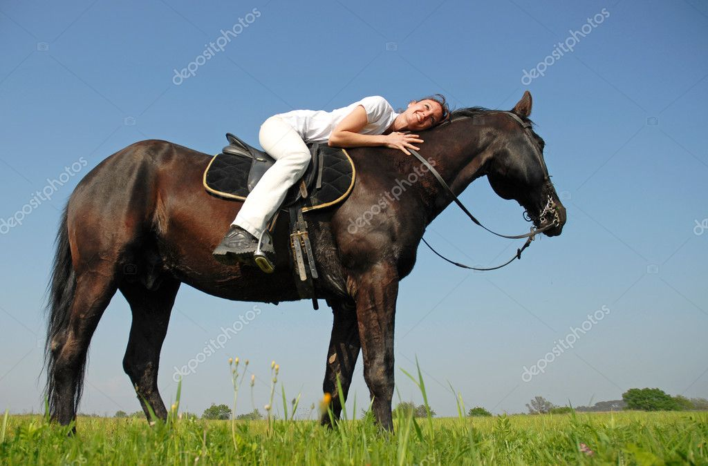 Young woman and her black stallion in a field in spring — Stock Photo #2768054