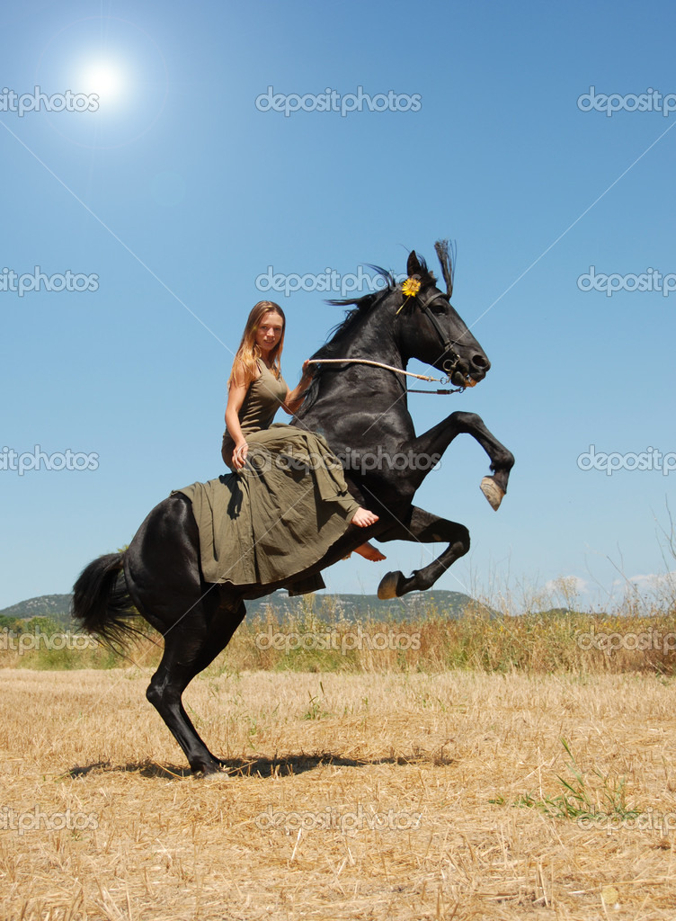 Young woman and her rearing stallion in a field in spring — Stock Photo #3093840