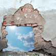 Blue sky hole in aged brick wall background — Stock Photo