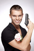 Man with pink rose and gun — Stock Photo