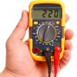 Hand with a digital multimeter on white — Stock Photo