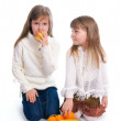 Two cheerful little girls with fruit — Stock Photo