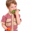 The little boy eats a cucumber on white — Stock Photo #3071958