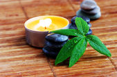 Spa stones with leaf and candle — Stock Photo