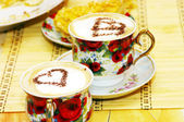 Cappuchino, with chocolate heart and cake — Stock Photo