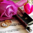 Stock Photo: Gold wedding rings and pink rose on note