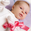 Baby girl with pink ribbon — Stockfoto