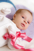 Baby girl with pink ribbon — Stock Photo