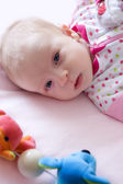 Baby girl lying on bed — Stockfoto