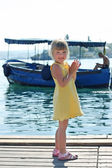 Girl on the beach on the background of the boat — Stok fotoğraf