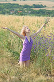 Beautiful girl in a lavender dress in a field — Stok fotoğraf