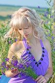 Vacker flicka i en lavendel klänning med en bukett blommor i — Stockfoto