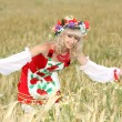 Beautiful girl in national dress and a wreath in the field of wh — Stock Photo