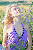 Beautiful girl in a lavender dress with a bouquet of flowers in — Stock Photo