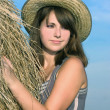 Beautiful girl in a straw hat near haystacks — Stock Photo
