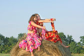 Two beautiful girls in bright dresses from top haystacks — Stock Photo