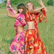 Two young girls dancing in a field — Stock Photo