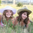 Two girls in hats lie on grass — Stockfoto #3552161