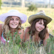 图库照片: Two girls in hats lie on grass