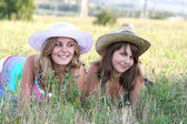 Two girls in hats lie on the grass — Stock Photo