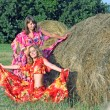 Royalty-Free Stock Photo: Two beautiful girls in bright clothes around haystacks