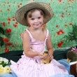 Beautiful girl in a straw hat fed duck — Stock Photo