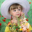 Beautiful girl in a hat with a bouquet of wildflowers — Stock Photo