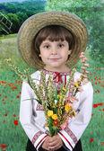 Hübscher junge mit strohhut mit einem blumenstrauß wildblumen — Stockfoto