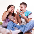 Young couple eating on the floor - Stock Photo