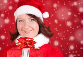 Smiling santa girl holding a gift — Stock Photo