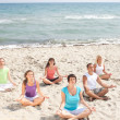 Meditation group on beach — Stock Photo