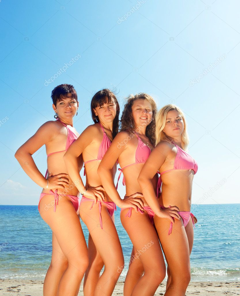 Sexy young girls in pink bikinis on sunny beach — Stock Photo #2925631