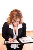 Blond geschäftsfrau schreiben in Dokumenten — Stockfoto