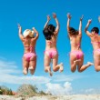 Four girls jumping on the beach — Stock Photo