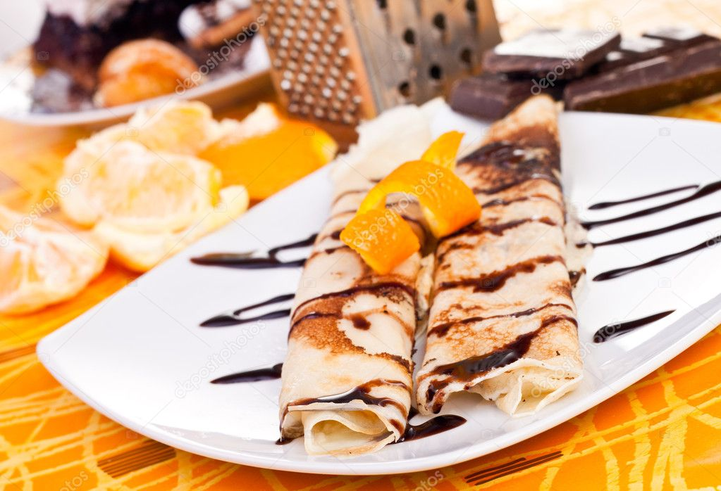 Plate of filled pancakes decorated with orange peel  Stock Photo #3274578
