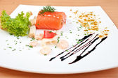 Delicious salmon on plate decorated with salad cheese and seafoo — Stock Photo