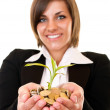 Woman holding a growing plant and coins — Stock Photo