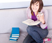 Girl reading a book on sofa — Stock Photo