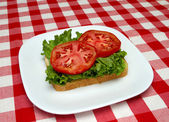 Slice of bread, lettuce and tomato - making a blt — Stock Photo