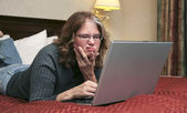 Woman on laptop in bed — Stock Photo