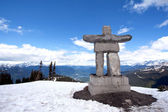 Whistler Peak inukshuk with snow and mountains — Stock Photo