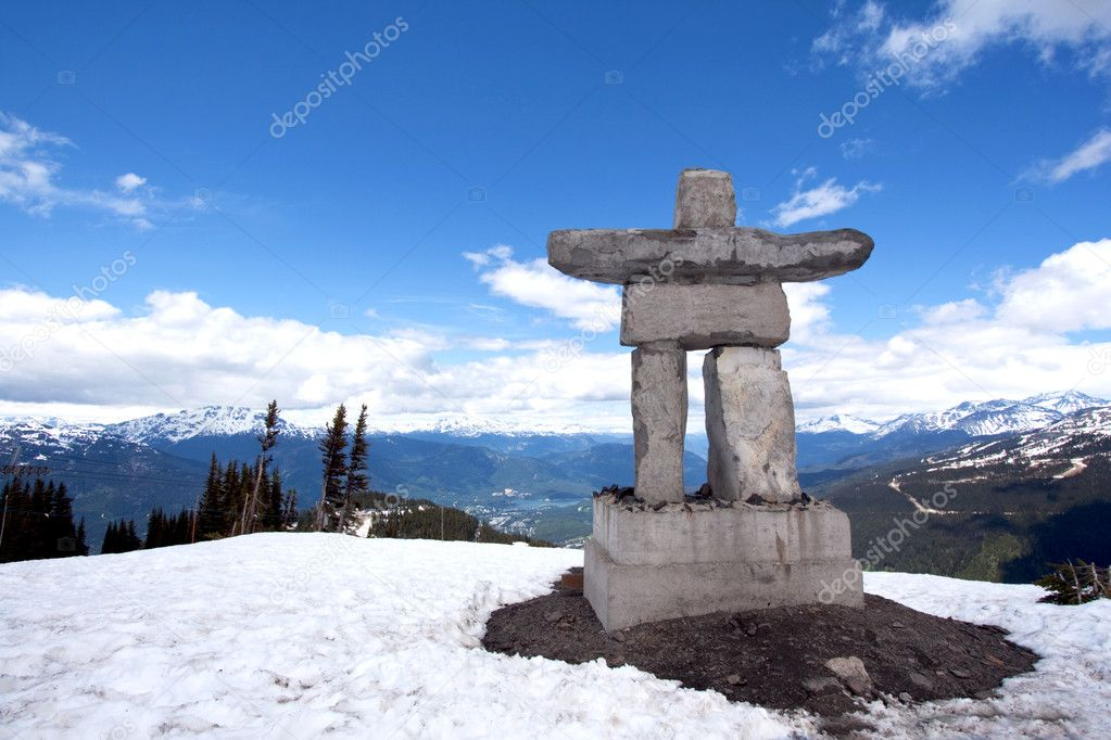 Inukshuk at the top of Whistler Peak in British Columbia, Canada, with snow, blue sky, white clouds and mountains in the distance — Stock Photo #3550571
