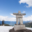 Whistler Peak inukshuk with snow and mountains vertical — Stock Photo
