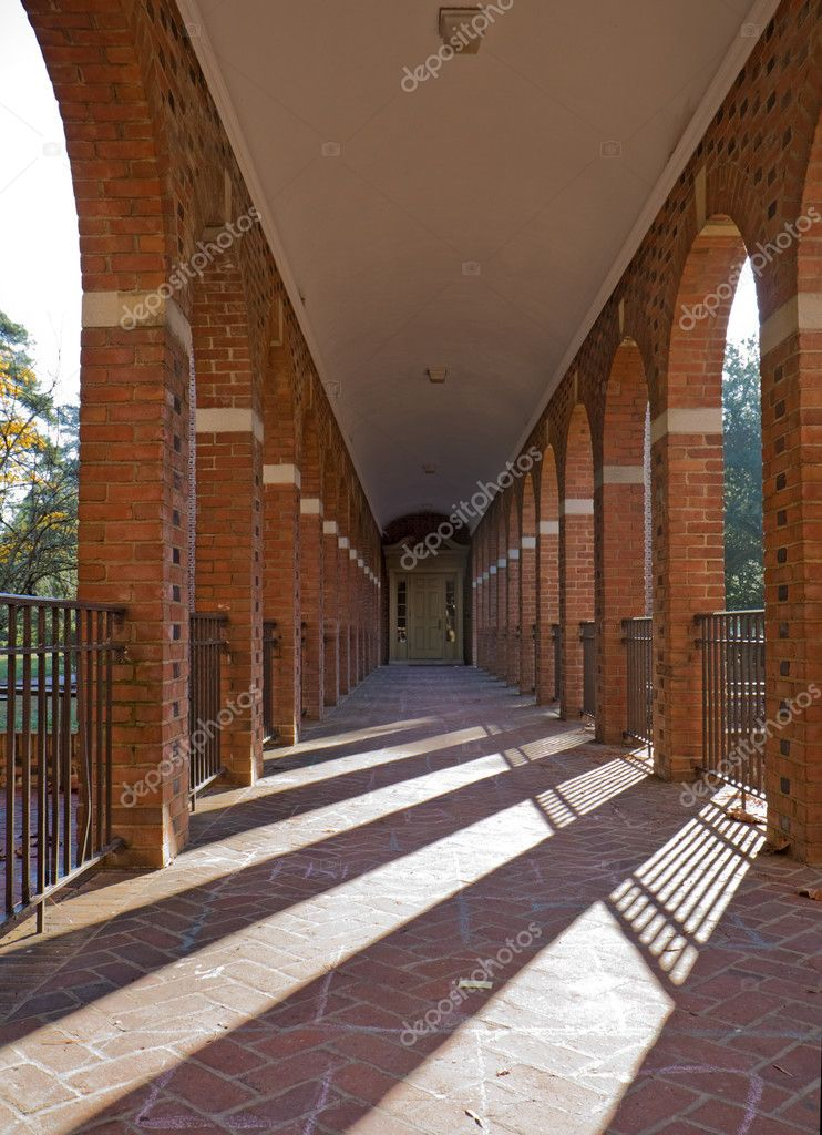 Arched walkway on the campus of the College of William and Mary in Williamsburg, Virginia, with slanting rays of the morning sun vertical — Stock Photo #3806199