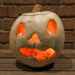 Lit white jack o'lantern on a bench — Foto de Stock