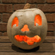 Lit white jack o'lantern on a bench — Stock fotografie